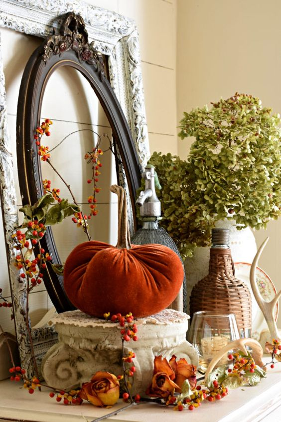 a rustic vintage Thanksgiving mantel with dried blooms, berries, leaves, antlers and vintage picture frames