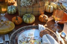 a rustic vintage Thanksgiving table with woven chargers, printed plates, natural pumpkins, a plaid box with hydrangeas