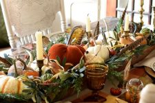 a rustic vintage Thanksgiving tablescape with a large bowl centerpiece with pumpkins, greenery, candles and feathers, plaid placemats, printed plates