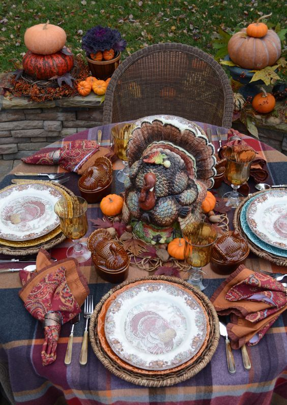 a rustic vintage Thanksgiving tablescape with a plaid tablecloth, bright napkins, a large turkey, colored glasses and mini pumpkins