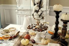 a rustic vintage Thanksgiving tablescape with neutral textiles, a striped runner, white porcelain and wooden stands with pumpkins plus cotton in a cloche