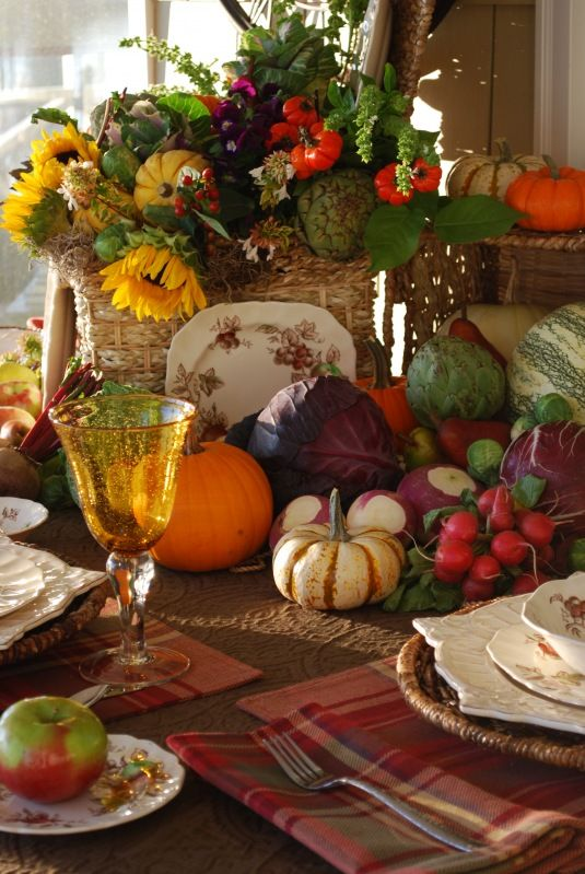 a rustic vintage Thanksgiving tablescape with plaid napkins, a veggie, greenery and bright sunflower centerpiece, colorful glasses