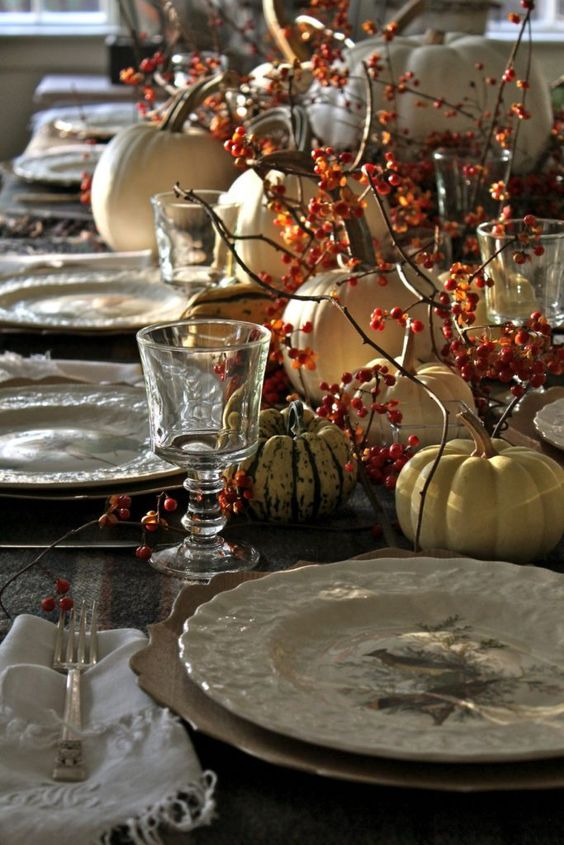a rustic vintage Thanksgiving tablescape with printed porcelain, berries, natural pumpkins and refined glasses