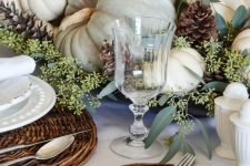 a rustic vintage Thanksgiving tablescape with woven chargers, white porcelain and textiles, natural pumpkins, greenery and pinecones