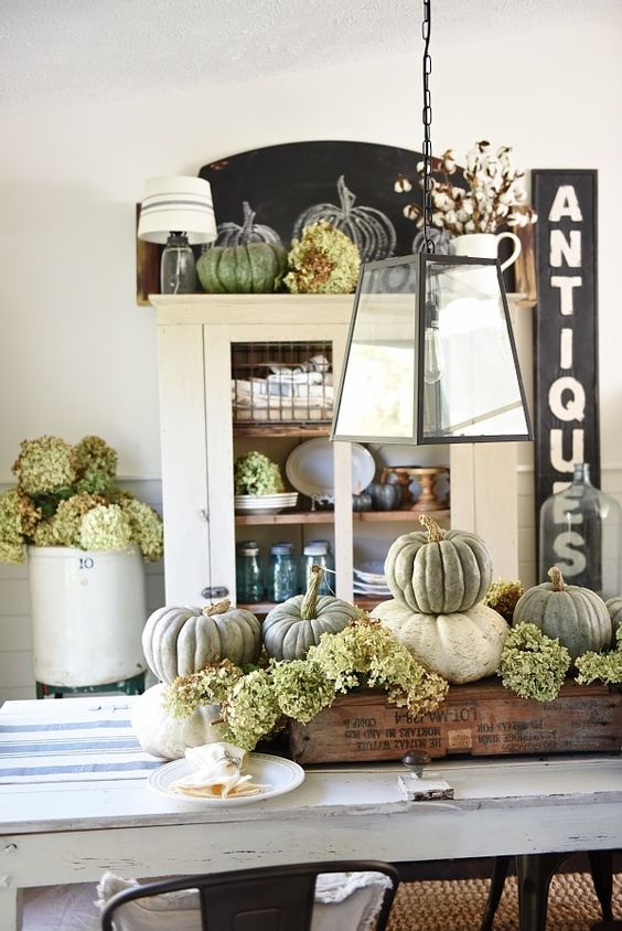 a rustic vintage centerpiece of a crate with green hydrangeas, natural pumpkins is ideal for Thanksgiving