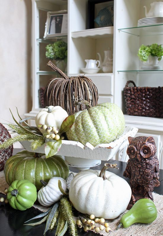 a rustic vintage centerpiece of white, green and vine pumpkins, berries and an owl is ideal for Thanksgiving