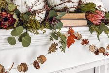 a rustic vintage mantel with greenery, pink blooms, white pumpkins and a garland with wood slices and nuts