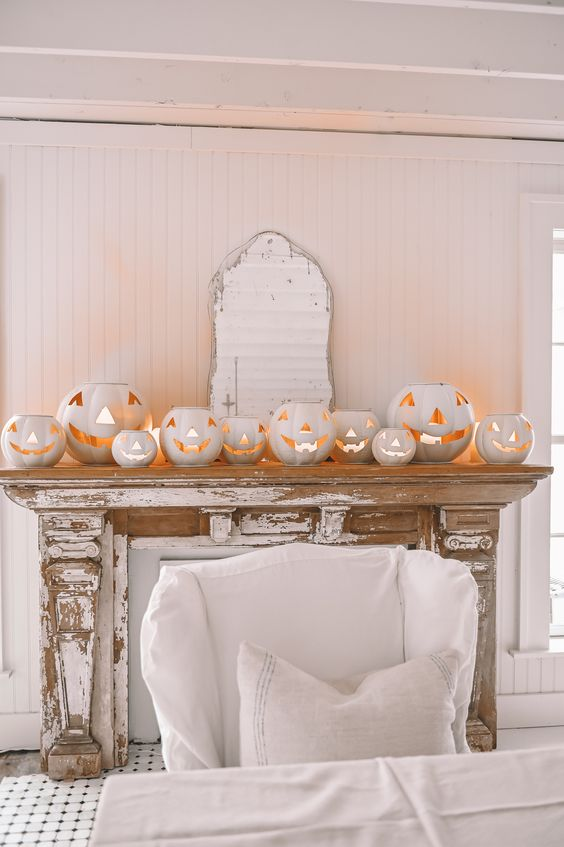 a shabby chic mantel styled with a lot of white jack-o-lanterns is a gorgeous and non-traditional idea for Halloween