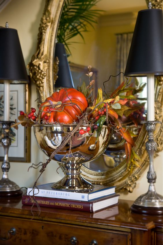 a shiny metallic bowl with faux pumpkins, greenery, berries and twigs for Thanksgiving decor