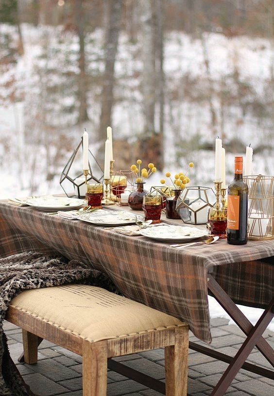 a simple and cozy Thanksgiving tablescape with candles, billy balls in apothecary jars, lanterns and a plaid tablecloth