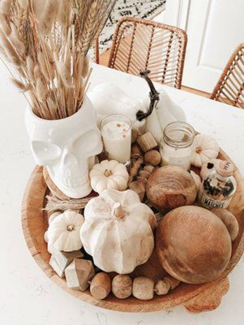 a simple fall to Halloween decoration fo a wooden bowl with wooden beams, gourds, candles, a skull vase with bunny tails is gerat