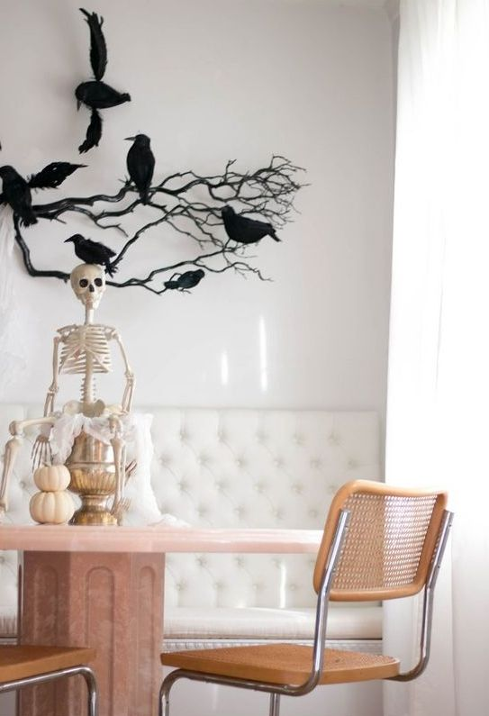a skeleton on a metallic jar, with a stack of pumpkins, black branches with blackbirds are amazing for Halloween decor