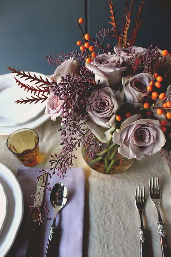 a sophisticated Thanksgiving tablescape with lilac napkins and a neutral tablecloth, lilac blooms, berries and vintage cutlery