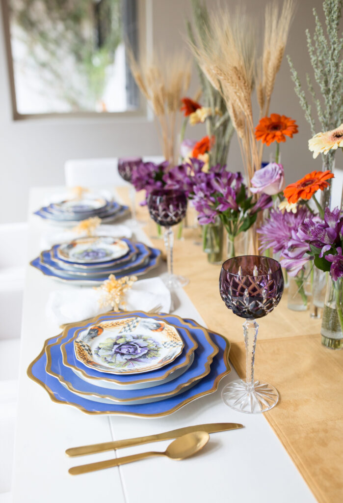 a stylish Thanksgiving table setting with a neutral runner, purple and orange blooms, wheat, blue plates with a gold edge, gold cutlery
