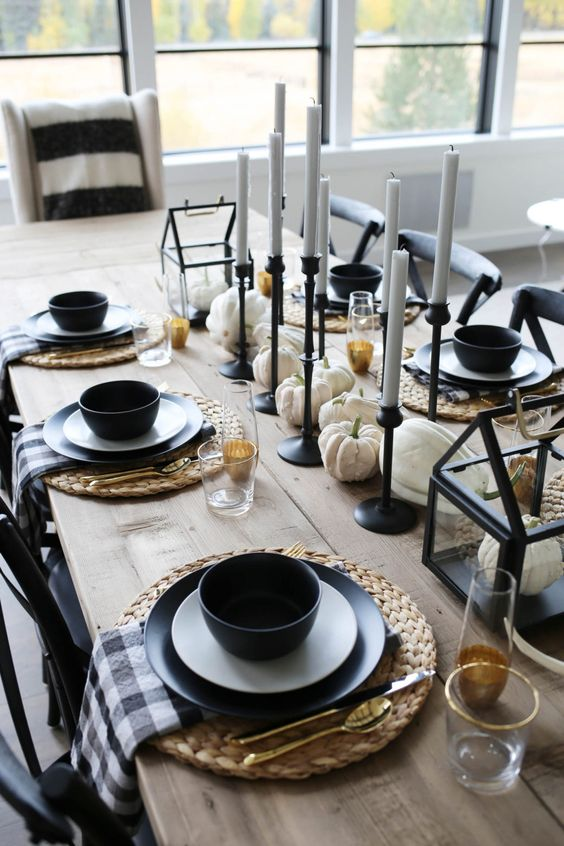 a stylish rustic Halloween tablescape with woven placemats, black plates and candleholders, white pumpkins and gold glasses