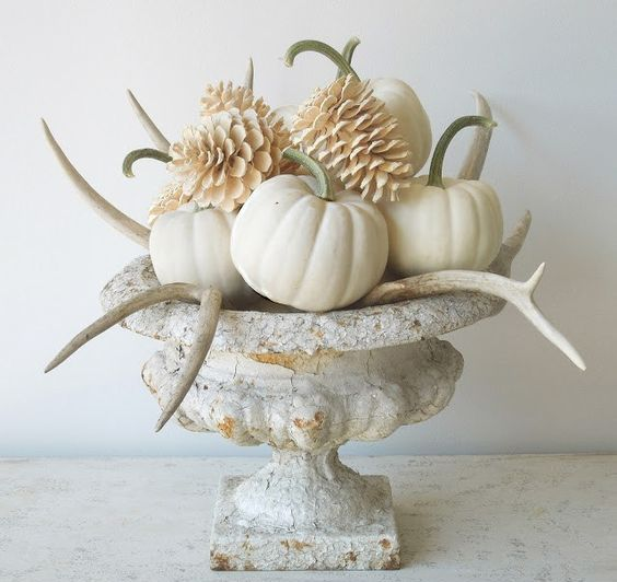 a stylish vintage Thanksgiving centerpiece of a vintage urn, bleached pinecones, antlers and pumpkins is chic