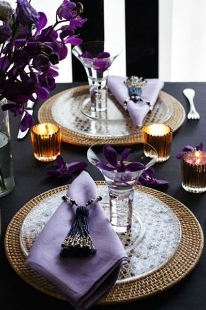 a super refined Thanksgiving tablescape with purple blooms and napkins, woven placemats, candles and beaded tassels