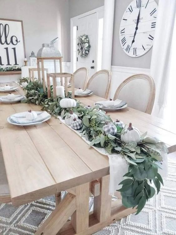 a table runner of greenery, white and plaid pumpkins and with candle lanterns is ideal for Thanksgiving