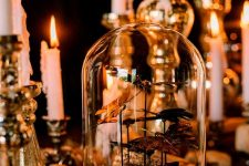 a vintage Halloween decoration of a cloche with faux butterflies, candles in gilded candlesticks, hay is chic