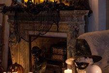 a vintage Halloween fireplace with black spiderweb and pillar candles, vintage candelabras, jack-o-lanterns and black faux blooms