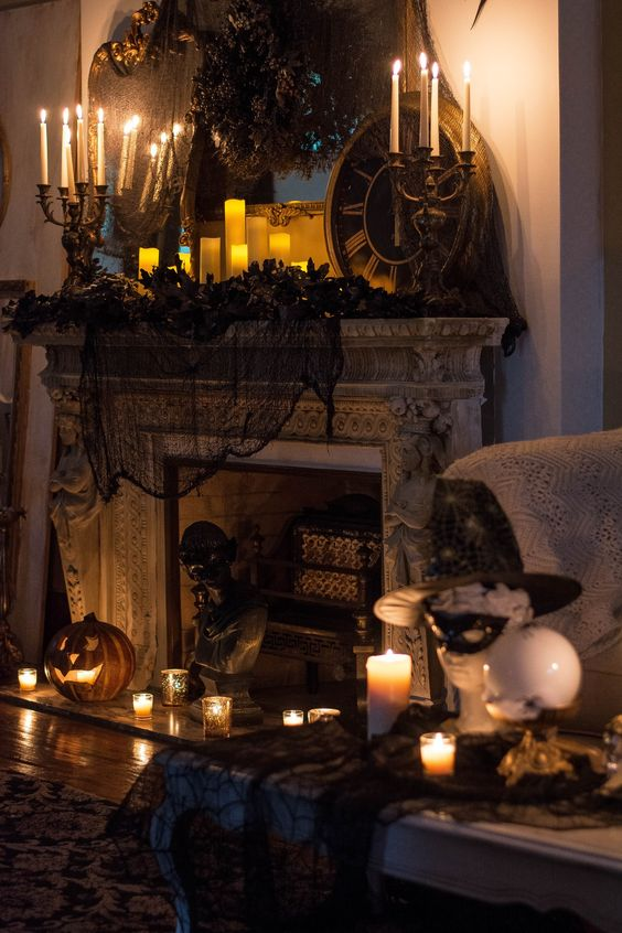 a vintage Halloween fireplace with black spiderweb and pillar candles, vintage candelabras, jack o lanterns and black faux blooms