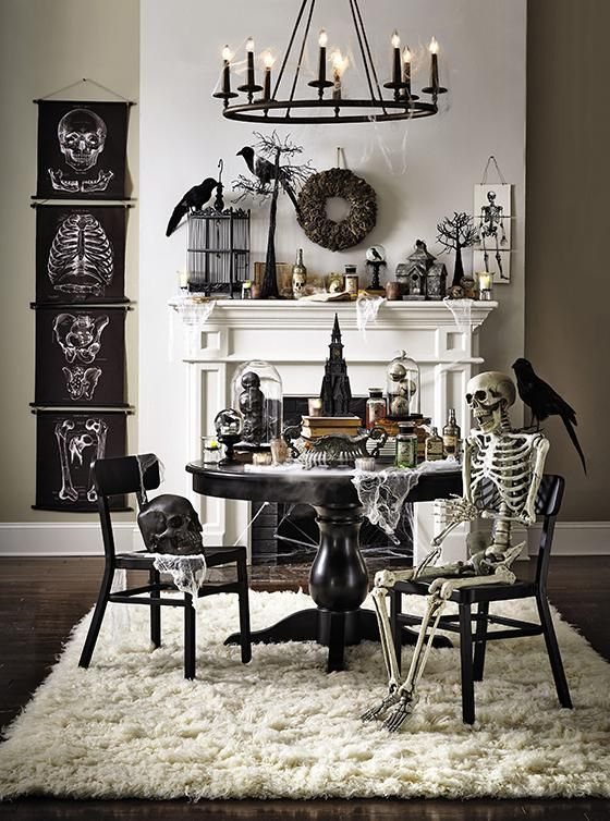 a vintage Halloween space with black posters, skeletons and skulls, blackbirds and wreaths, black furniture and a candle chandelier is wow