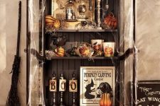 a vintage Halloween storage unit in black, with pumpkins, gourds, candles, signs and a broom by its side is a lovely idea for your party