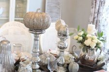 a vintage Thanksgiving table with mercury glass stands, silver glitter pumpkins, turkey, white blooms and pink and white porcelain