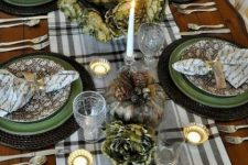 a vintage Thanksgiving tablescape with a plaid runner, green and floral plates, quote napkins,a gold pumpkin and candleholders