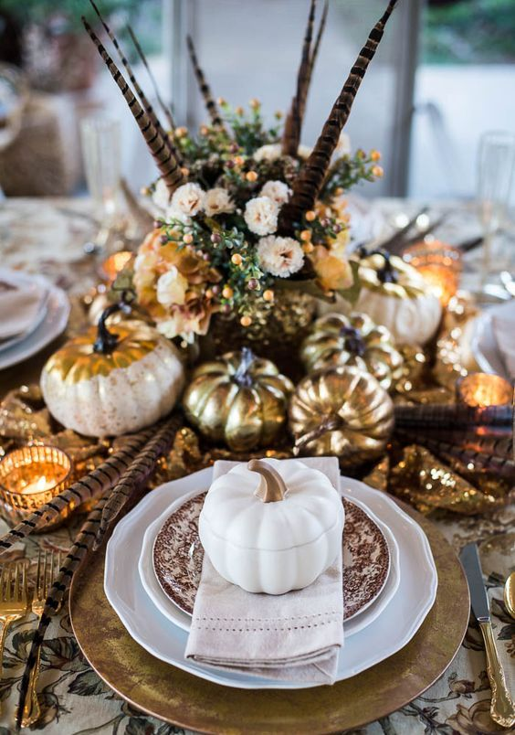 a vintage boho Thanksgiving tablescape with printed linens and plates, gold chargers, cutlery, pumpkins and candleholders, feathers and blush blooms