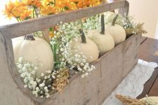 a vintage rustic Thanksgiving centerpiece of a wooden box with white pumpkins, orange blooms and baby's breath
