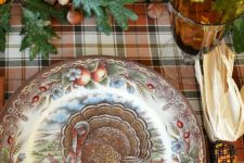 a vintage rustic Thanksgiving table with a plaid tablecloth, a printed plate, leaves, acorns, pumpkins and candles