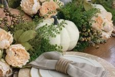 a vintage rustic Thanksgiving table with wooden chargers, burlap placemats, faux greenery, berries, peachy blooms and pumpkins