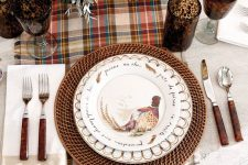 a vintage rustic Thanksgiving tablescape with a plaid runner, woven chargers, printed plates, vintage cutlery and bold blooms and glasses