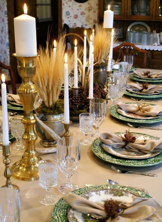 a vintage rustic Thanksgiving tablescape with printed plates, wheat, pinecones, gold candleholders and refined glasses