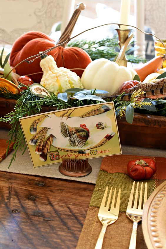 a vintage rustic centerpiece of a wooden box with greenery, gourds, pumpkins and feathers and a vintage card