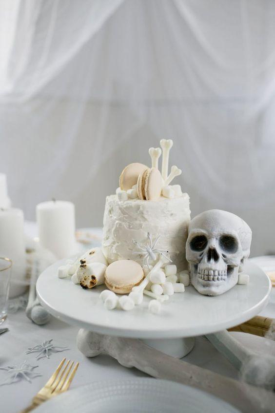 a white Halloween cake with edible bones, a skull, marshmallows and macarons is an adorable idea