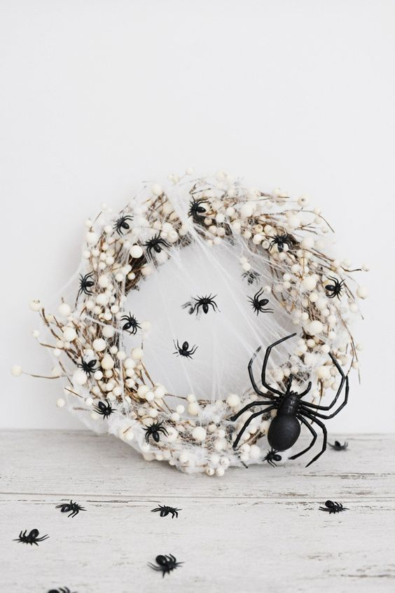 a white Halloween wreath imitating spider eggs covered with black spiders is a bold and catchy idea for your white Hallwoeen party