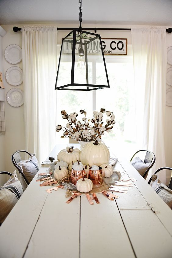 a white fall and Thanksgiving centerpiece of white pumpkins, cotton, copper mugs and a letter banner