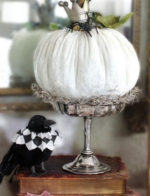 a white pumpkin on a stand, with a black spider and a crown plus green leaves and hay is a cool decoration for Halloween