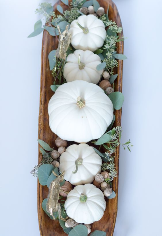 a wooden plate with white pumpkins, leaves, nuts and acorns is a great Thanksgiving centerpiece to make in a minute