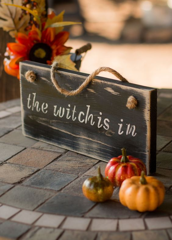 a wooden sign paired with some faux pumpkins for chic and stylish Halloween decor