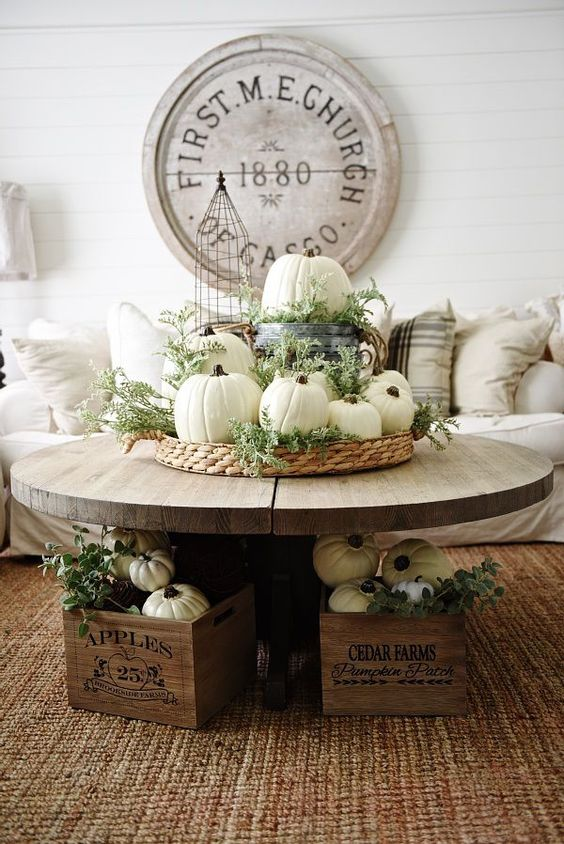 a woven basket with white pumpkins, greenery, a bucket with a pumpkin and crates with them for Thanksgiving and fall