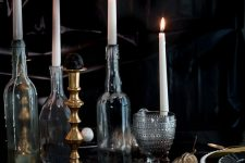 an elegant vintage Halloween tablescape with black and gold plates, tall candles in bottles, chic glasses and dried blooms on the table