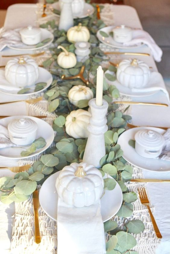 an elegant white Thanksgiving tablescape with white pumpkins, porcelain, candles, a woven table runner, a eucalyptus table runner