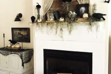 chic vintage fireplace styling with greenery, pumpkins, bats, portraits, books and some spider web here and there
