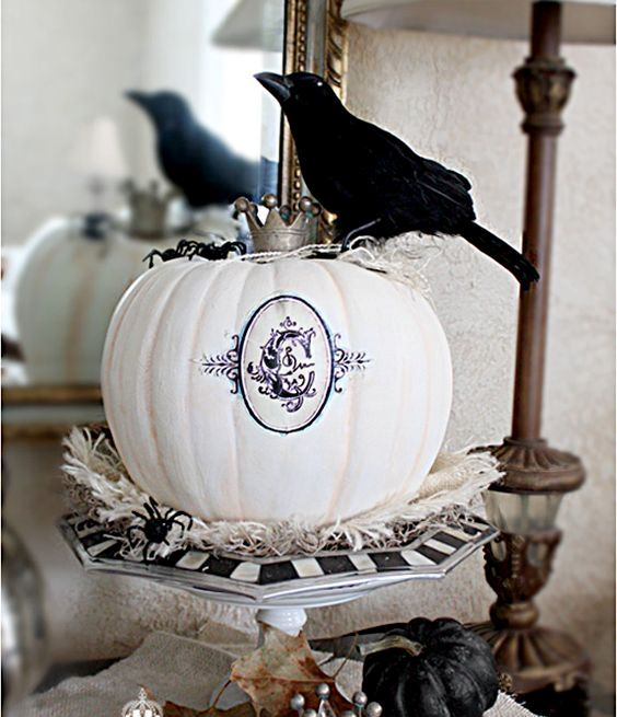 elegant vintage Halloween decor with a black and white stand, a white printed pumpkin with a crown and a black pumpkin and a blackbird