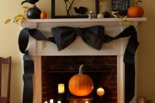 elegant vintage Halloween decor with candles and a pumpkin in the fireplace, a black black bow, blackbirds, pumpkins and leaves