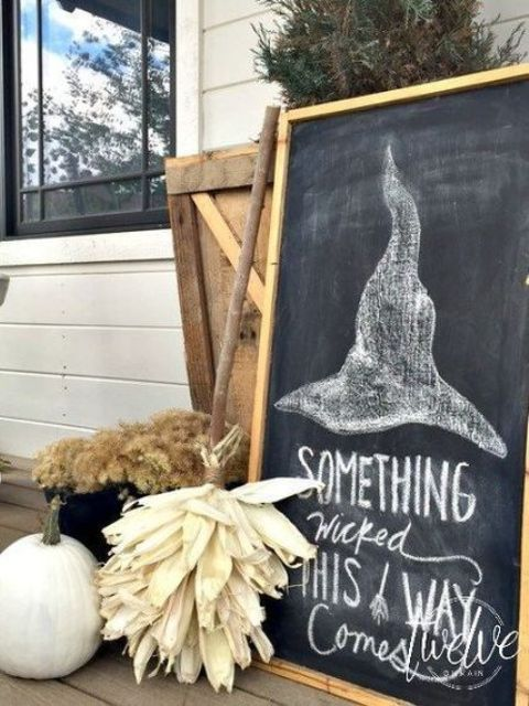 farmhouse Halloween decor with a chalkboard, a broom of husks, dried blooms and a white pumpkin is very cozy