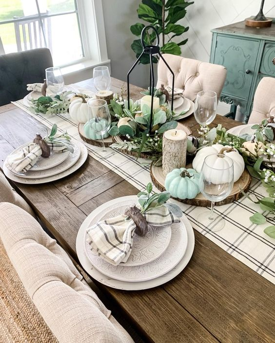 faux greenery and faux green and white pumpkins, a plaid runner and wood slices for pretty rustic Thanksgiving decor